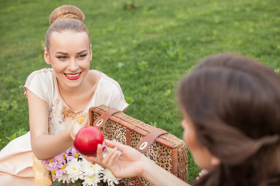 Cheerful women are sitting on green grass near a basket of food and flowers. The blond lady is giving an apple to her friend. She is looking at her with joy and smiling